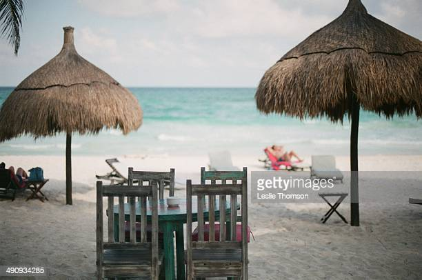 White sand beach with table and chairs.