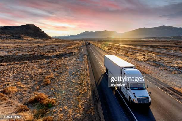 weißer sattelzug auf einer vierspurigen autobahn bei dämmerung - konvoi stock-fotos und bilder