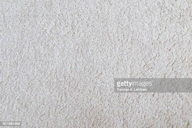 White shaggy carpet texture background viewed from above.