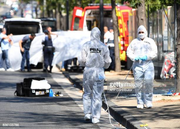 A white sheet is erected as a body of a victim is evacuated to a waiting ambulance while French forensic police officer search the site following a...