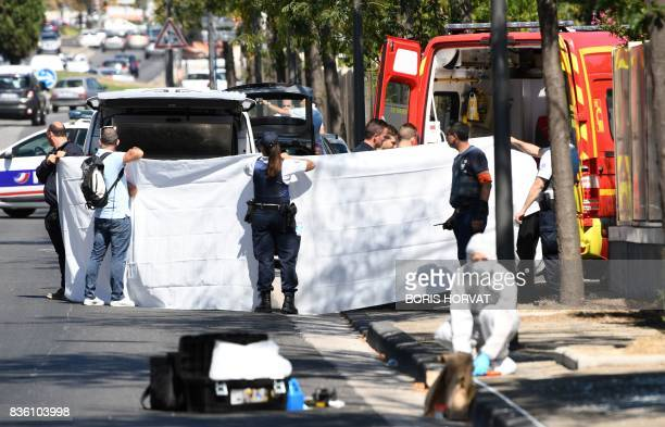 TOPSHOT A white sheet is erected as a body of a victim is evacuated to a waiting ambulance while French forensic police officer search the site...