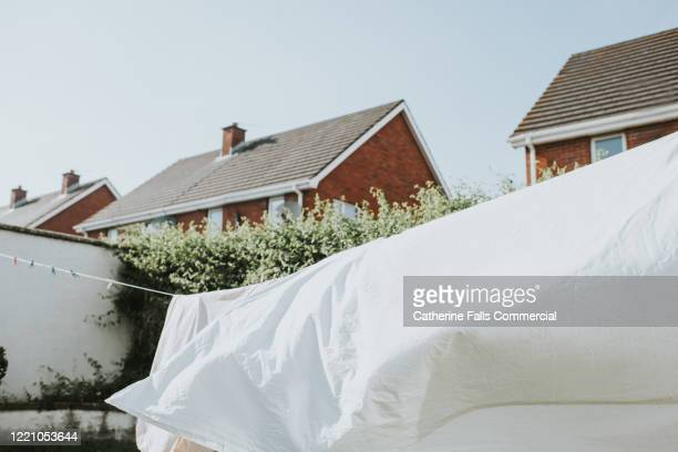 white sheet on washing line - launderette stock pictures, royalty-free photos & images