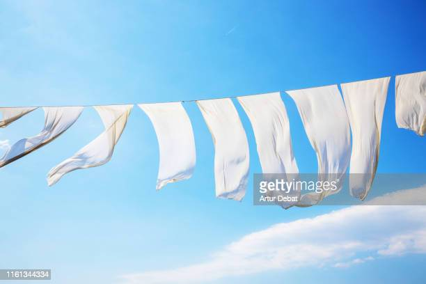 white sheets flying with the wind and blue sky in greece. - 物干し ストックフォトと画像