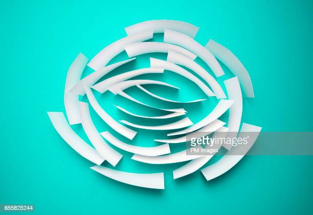 White sheets of paper in circular pattern on green