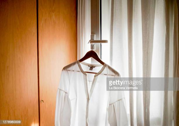 white shirt hanging on the window - white shirt stock pictures, royalty-free photos & images