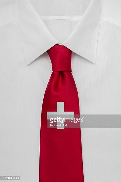 A white shirt with a Swiss Flag tie