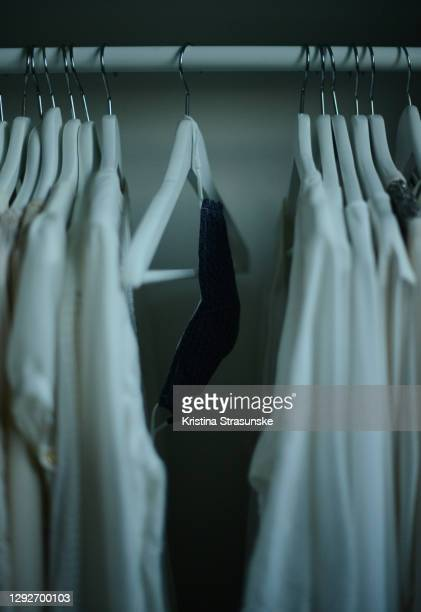 white shirts hanging on coathangers on a clothing rack along with reusable protective covid face mask - white shirt stock pictures, royalty-free photos & images