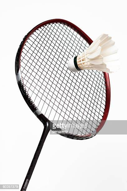 white shuttlecock and badminton racket