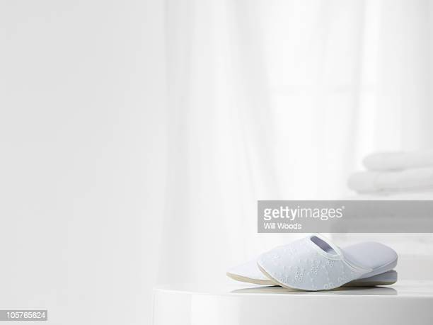 White slippers with white towles in the background