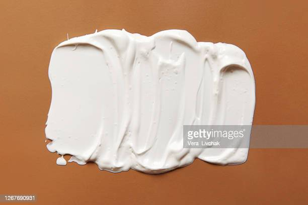 white smear of cream or oil on a pastel beige background. flat lay style. - painting art product stock pictures, royalty-free photos & images