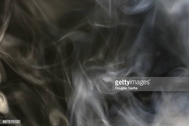 White smoke from a cigar on a black background
