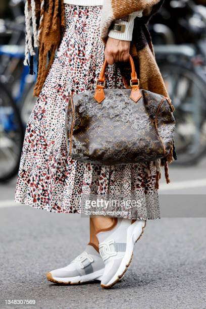 White sneakers by Todt's and a brown bag by Louis Vuitton as a detail of German TV host and communication manager Bettina Cramer, during a...