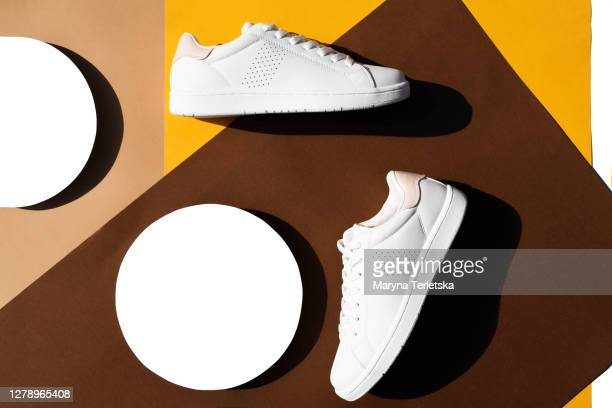 white sneakers on a multicolored background in a geometric style. - witte schoen stockfoto's en -beelden