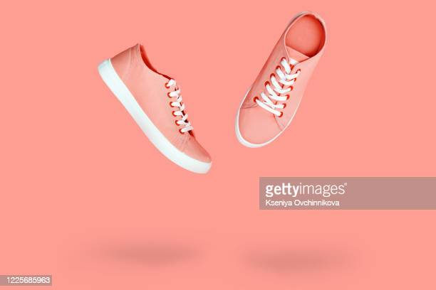 white sneakers with purple laces on yellow background. modern minimal fashion art trendy bold color still life - purple shoe stock pictures, royalty-free photos & images