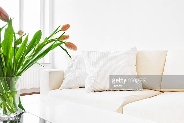 A white sofa and tulips in a modern living room