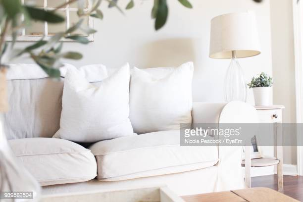 white sofa by table at home - cushion stock photos and pictures