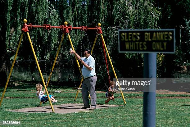 A White South African father watches his two young children playing on a swing set near an apartheid sign reading SlegsBlankesWhites Only in a public...