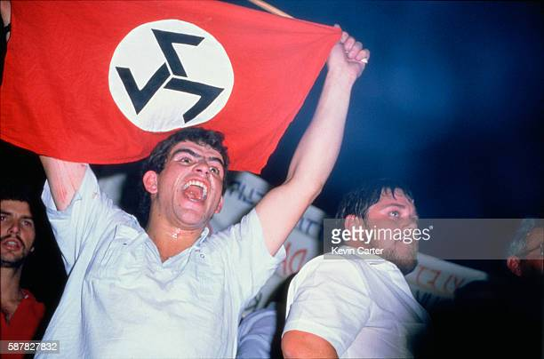 White South African man holds up a flag for the Afrikaner Resistance Movement disrupting a National Party meeting in Pietersburg