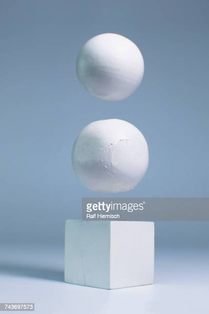 White spheres levitating over block shape against gray background