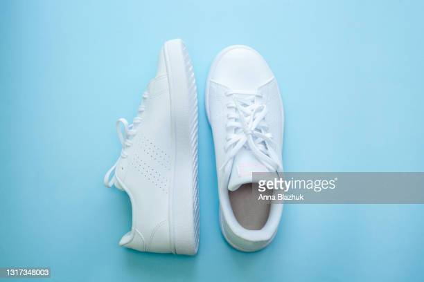 white sports shoes over blue background, sports and casual clothing style concept. summer or spring fashion. - footwear stock pictures, royalty-free photos & images