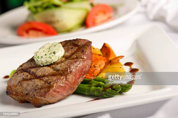 A white square plate containing grilled steak and salad