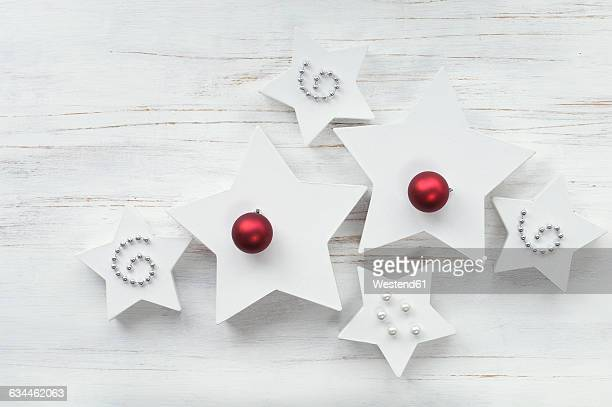 White star-shaped Christmas presents, with Christmas decoration on wood