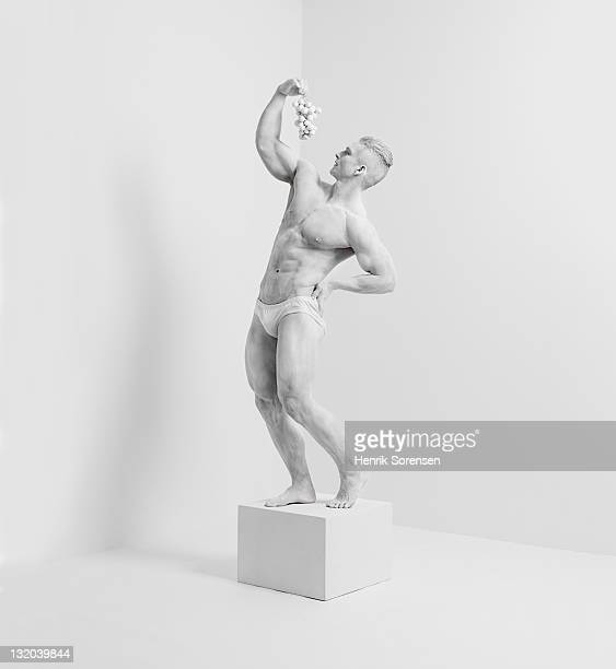 white statue in white room with grapes
