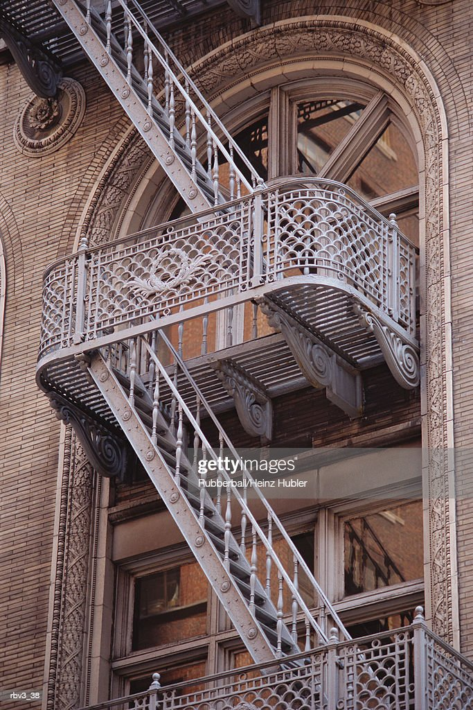 white steel ladders rise from glass windowed level to another of New York apartments : Stockfoto
