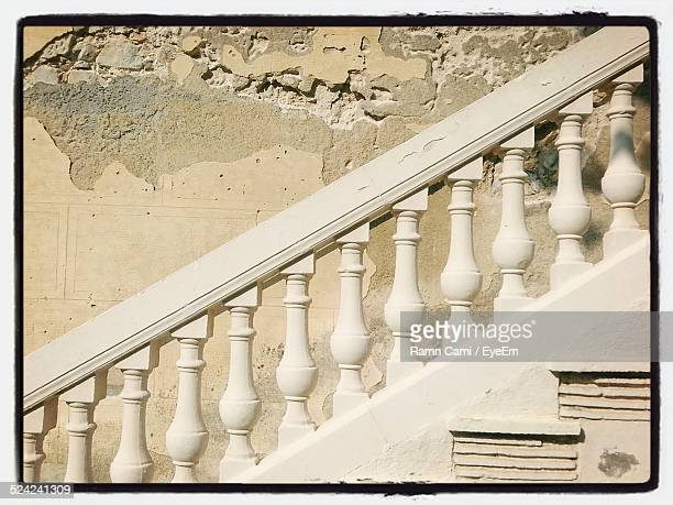 White Stone Balustrades Against Damaged Wall