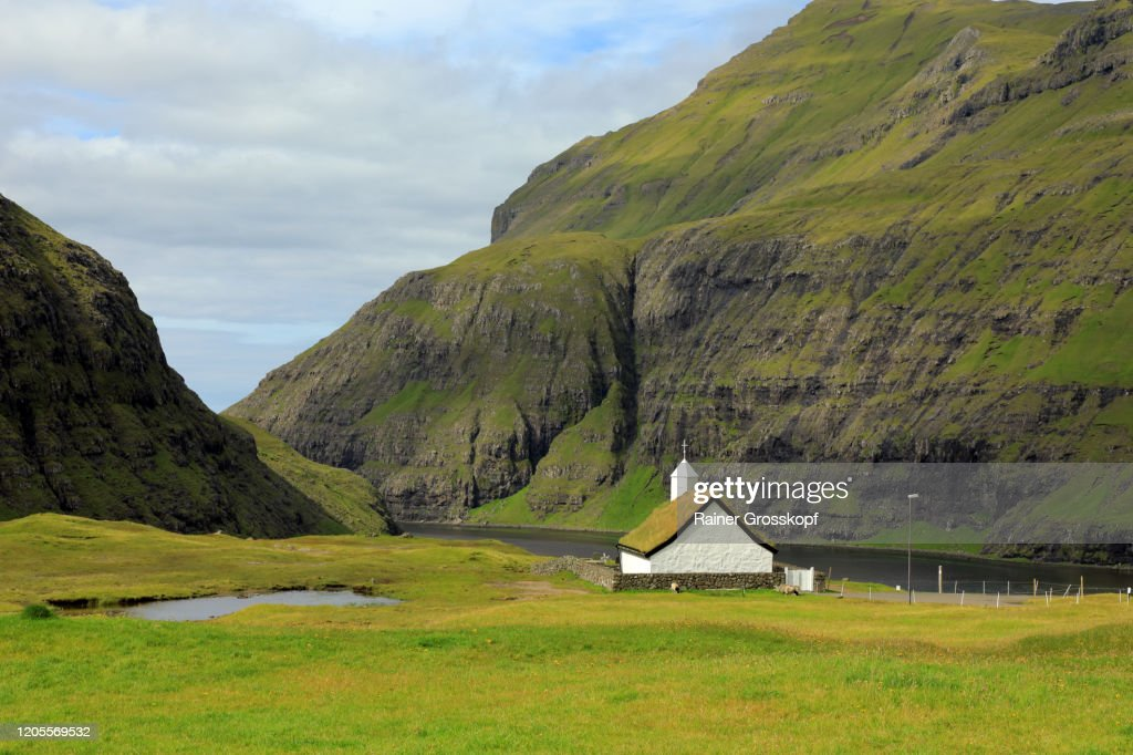 A white stone church with a grassy roof above a bay between high mountains : Stock-Foto