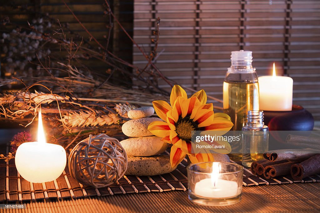 white stones, dried flowers, candles, oil, on mat : Stock Photo