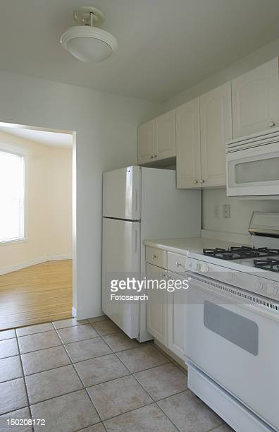 White stove and kitchen in empty apartment