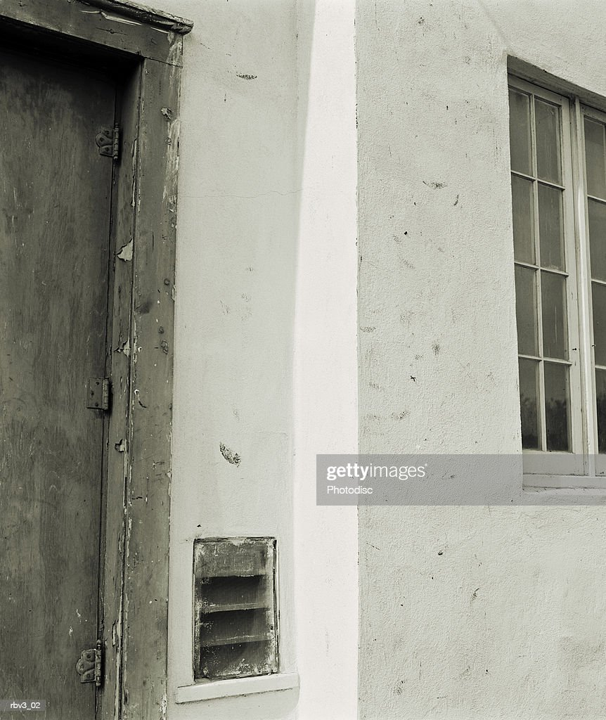 white stucco Mexican mission style wall with window and gray door : Foto de stock