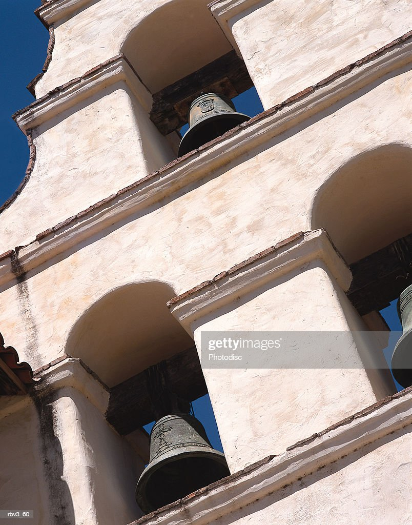 white stucco walls house bells in Mexican mission style buildings below a blue sky : Foto de stock