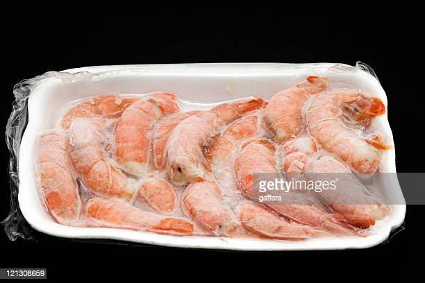 A white Styrofoam tray full of frozen shrimp