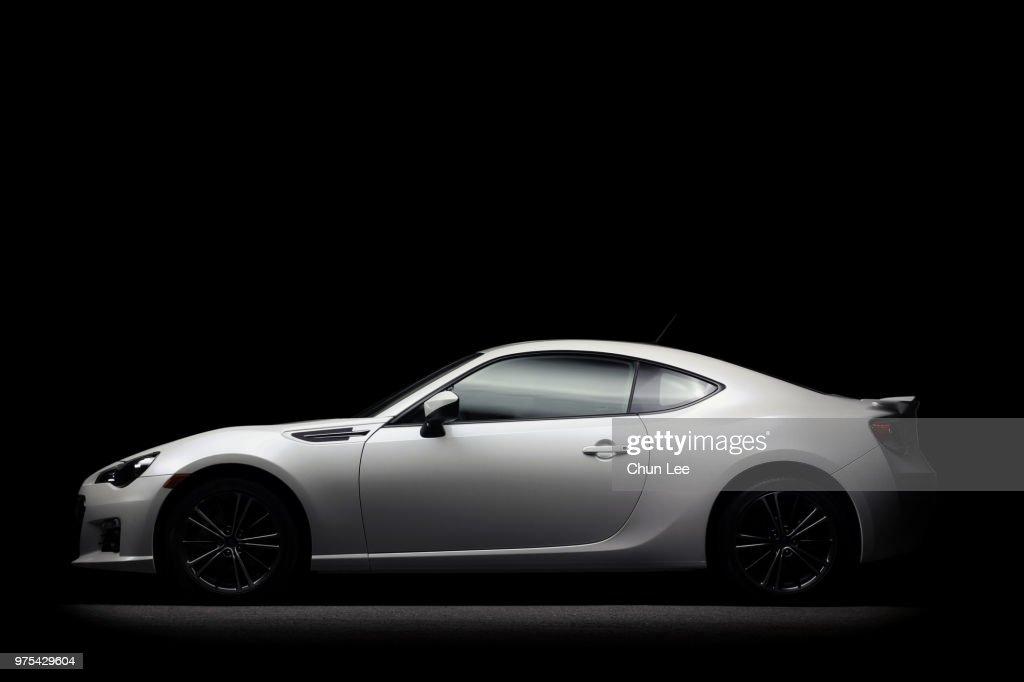 White Subaru car on a black background : Stock Photo