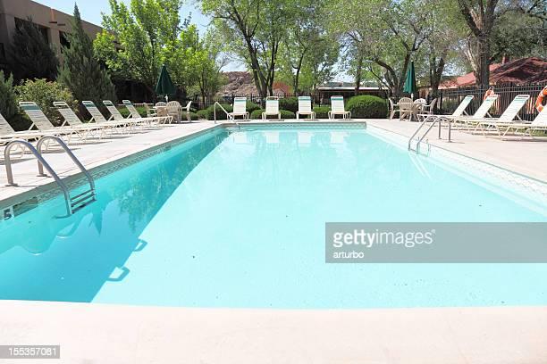 Blanco turquesas, las sillas reclinables alrededor de la piscina, frente a cielo azul