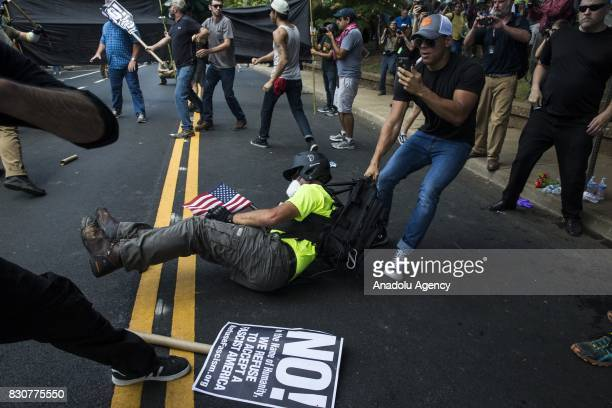 A White Supremacist drags a buddy to safety after he was beat by counter protestors during clashes at Emancipation Park where the White Nationalists...
