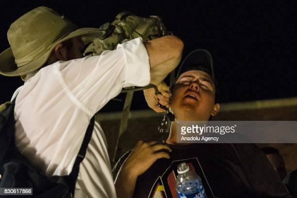 White Supremacist helps another after he was hit with pepper spray during a clash between counter protestors and Neo Nazis AltRight and White...