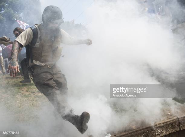 A White Supremacist kicks back a smoke bomb thrown by counter protestors during clashes at Emancipation Park where the White Nationalists are...