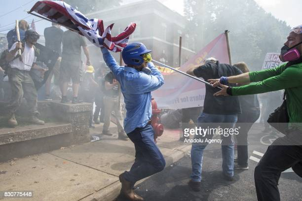 August 12: A White Supremacist tries to strike a counter protestor with a White Nationalist flag during clashes at Emancipation Park where the White...