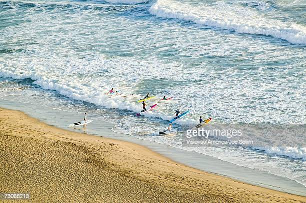 """""""white surf and beach where surfer school sets out for surfing in durban, south africa on the indian ocean"""" - durban beach stock photos and pictures"""