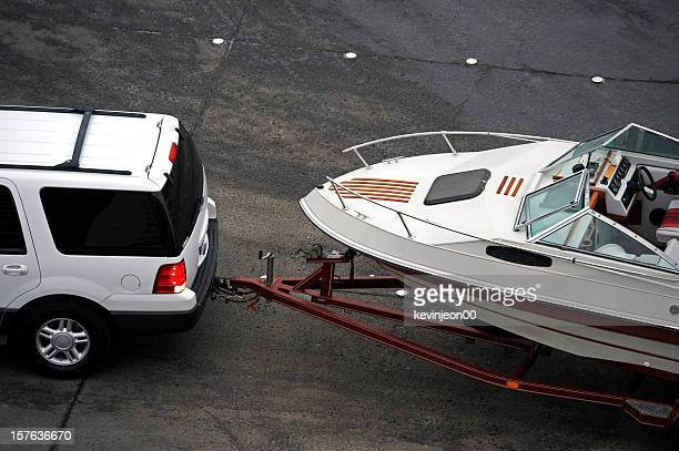 White SUV pulling white speed boat on trailer from above
