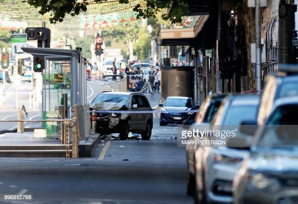 A white SUV sits in the middle of the road as police and emergency personnel work at the scene of where a car ran over pedestrians in Flinders Street...
