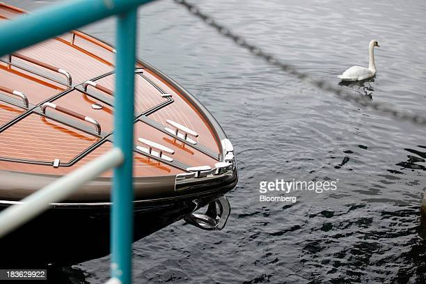 A white swan swims in Lake Isea near a Riva Rivarama Super luxury yacht manufactured by Ferretti Group at the company's shipyard in Sarnico Italy on...