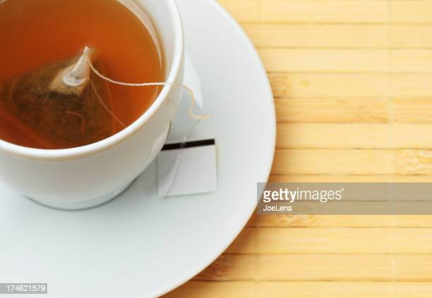 White tea cup with steeping tea bag on a light wooden table