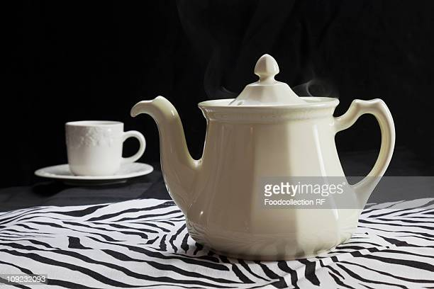 White tea pot and tea cup on zebra pattern cloth