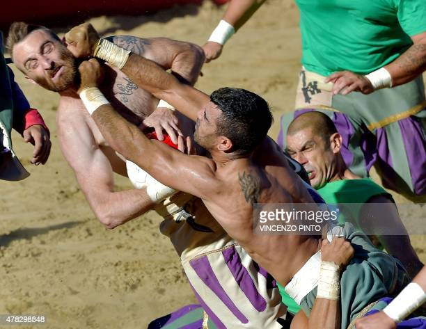 A White Team player is tackled by two Green Team players during their Calcio Fiorentino match in Florence's Piazza Santa Croce on June 24 2015 Calcio...
