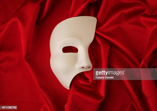 white theatrical mask on red satin background - masque tissus photos et images de collection