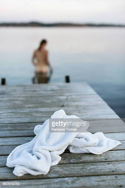 White towel on jetty with naked woman in lake